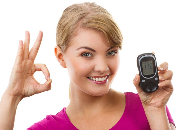 Happy woman holding glucose meter with positive result of measurement sugar level and showing sign ok, concept of diabetes, checking sugar level
