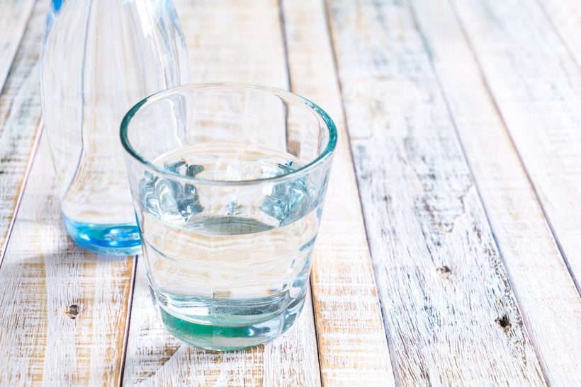 Water in a glass on a wooden background.