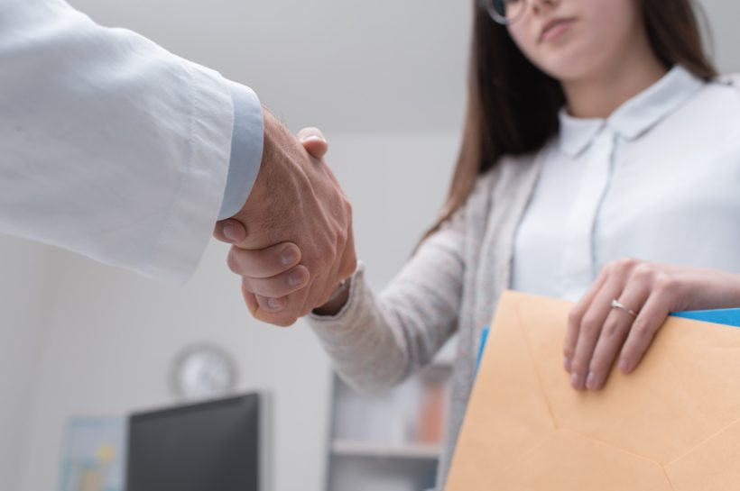 Doctor shaking hands to the female patient in the office, she is holding medical records, hands close up